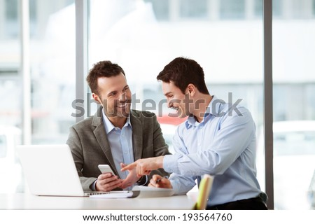 Two young professionals looking at a smartphone - stock photo