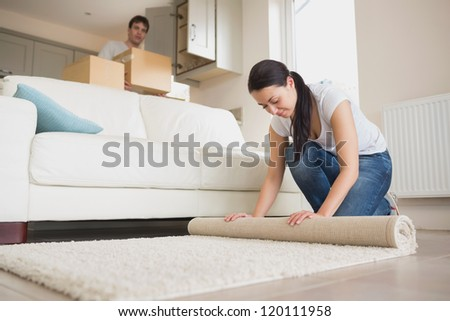 Two young relocating people moving into their house and furnishing the lounge - stock photo