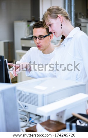 Two young researchers carrying out experiments in a lab (shallow DOF; color toned image) - stock photo