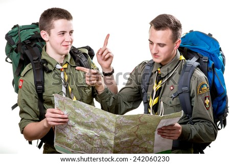 Two young scout boys with backpacks holding the map and showing the right way isolated on white background - stock photo
