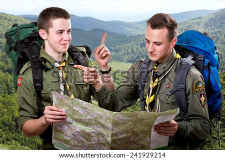 Two young scout boys with backpacks holding the map and showing the right way traveling in the mountains - stock photo