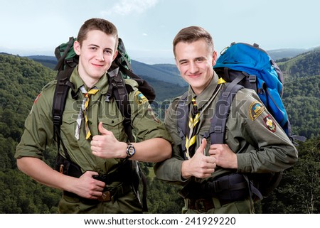 Two young scout boys with sleeping bag and backpack traveling in the mountains - stock photo