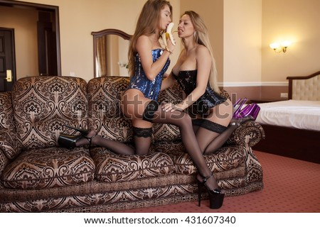Two Young sexy blonde and brunette woman eats and play with banana on sofa.Blurred background.