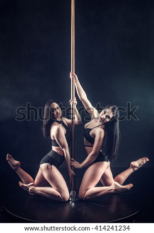 Two young sexy pole dance women - stock photo