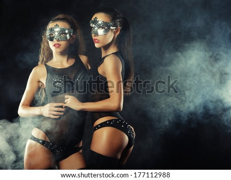 two young sexy striptease dancer with mask - stock photo