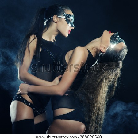 two young sexy striptease dancer with mask, dance in smoke - stock photo