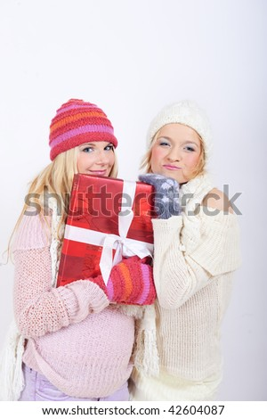 two Young sexy winter woman in knit clothes, hat and scarf and gloves giving christmas presents