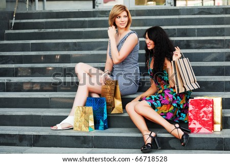Two young shopper on the steps. - stock photo