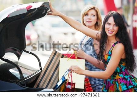 Two young shoppers in a car parking - stock photo