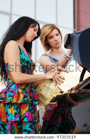Two young shoppers with a car - stock photo