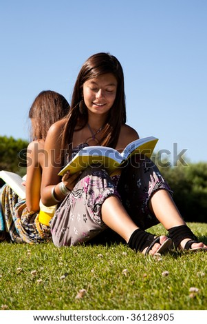 two young sisters at the park reading a book