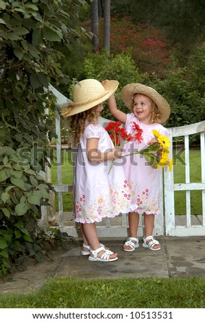 Two young sisters play in park besides a white wooden gate.  One girl lifts the brim of her sister's hat. - stock photo