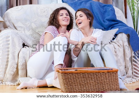 Two young sisters sitting on the floor, in living room, talking memories and having a good time. Indoors, friends, family concept.  - stock photo