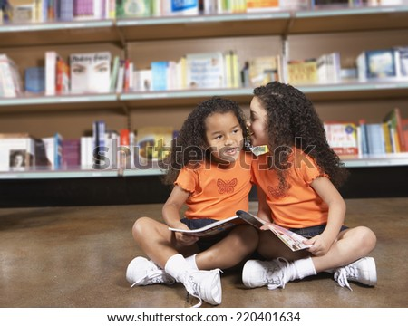 Two young sisters whispering in library - stock photo