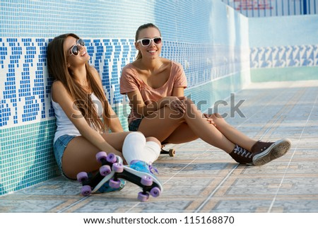 Two young skateboarding and roller skating girl friends sitting in empty swimming pool, outdoors