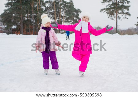 two young skater girls on the ice of the frozen lake. kids on the background