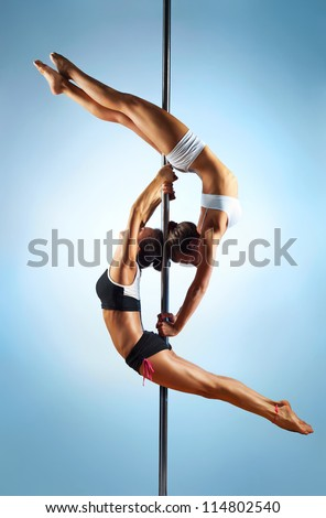 Two young slim pole dance women. - stock photo