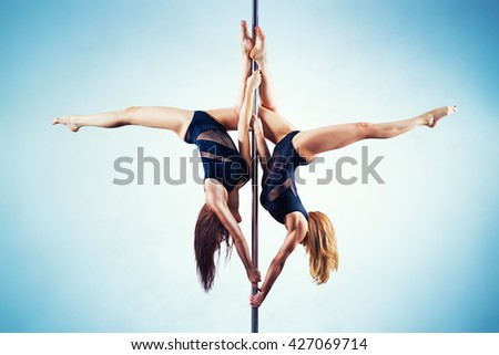 Two young slim pole dance women on white and blue wall background - stock photo