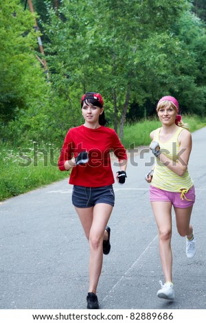 Two young slim women running on the road - stock photo
