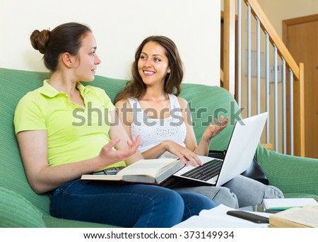 Two young smiling female students sitting on sofa and doing homework at home