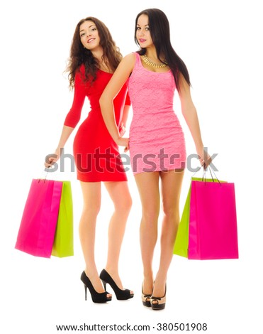 Two young smiling girls with bags isolated - stock photo