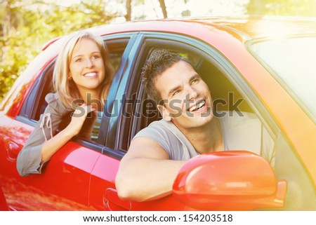 Two young smiling people in a red car - stock photo