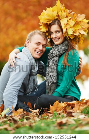 Two young smiling people with autumn maple leaves in park at fall outdoors date - stock photo
