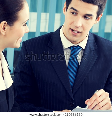 Two young smiling successful businesspeople signing document at office - stock photo