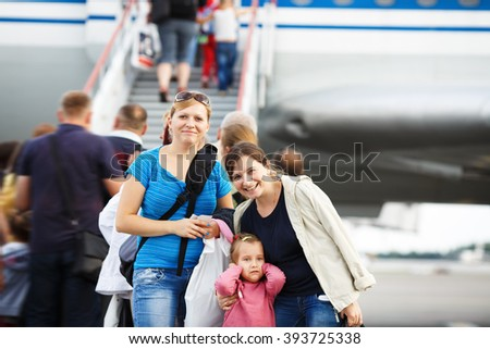 Two young smiling women and child girl posing in the blurry background ladder passenger aircraft at the airport. Passengers on the airliner background. Shallow depth of field. Selective focus. - stock photo