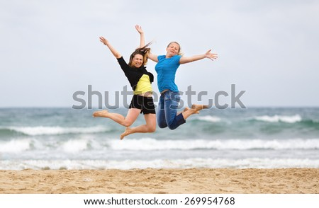 Two young smiling women jumping on the beach against the sea and cloudless sky. Shallow depth of field. Focus on the models. - stock photo