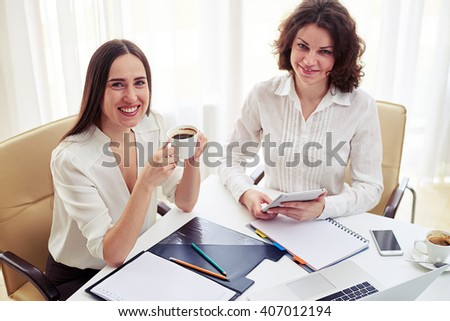 Two young smiling women teamworking with gadgets and drinking coffee  in the modern office - stock photo