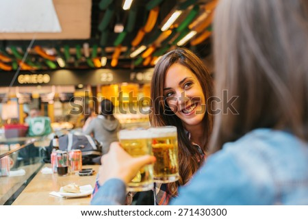Two Young Spanish Women Having a Drink in a Traditional Market - stock photo