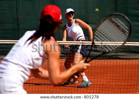 Two young sporty female tennis players enjoying a game in the sun on the Costa del Sol - stock photo