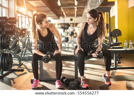 Two young sporty women lifting weights at gym.
