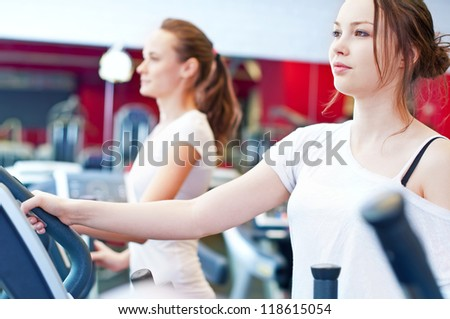 Two young sporty women run on machine in the gym centre - stock photo