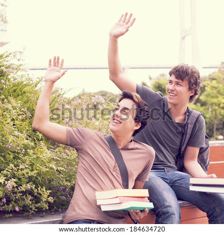 two young student gesturing at  school (selective focus) - stock photo