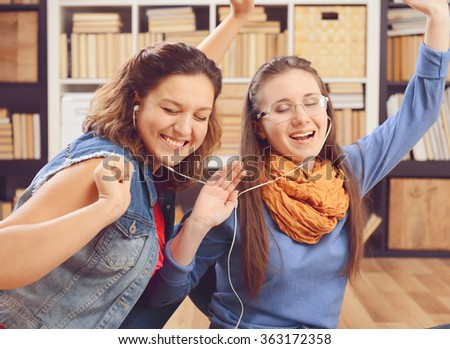 Two young student girl listening to music on headphones - stock photo