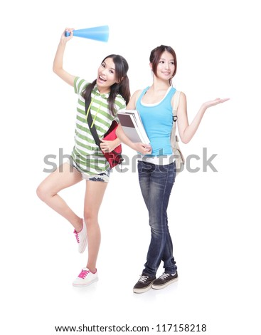 Two young student girls happy showing something to empty copy space by palm in full length. Isolated on white background. cute asian women model