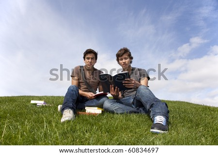 two young student reading books at the school park - stock photo