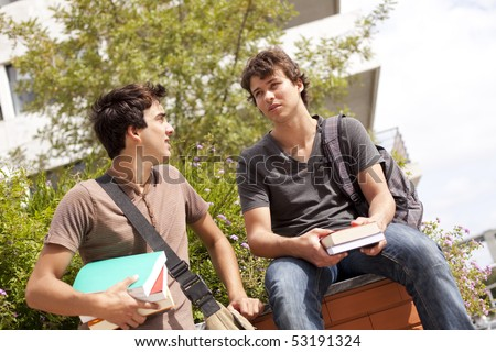 two young student talking at the school (selective focus) - stock photo