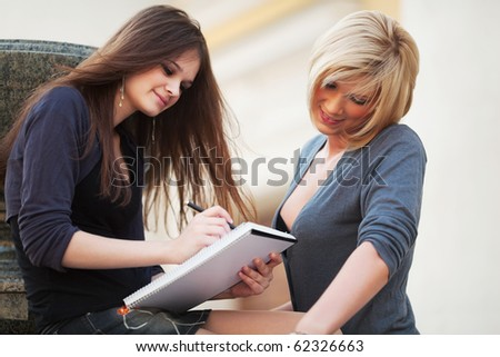Two young students on campus. - stock photo