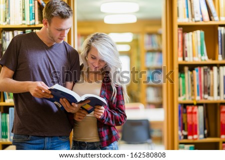 Two young students reading book against bookshelves in the library