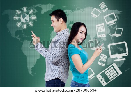 Two young students sending message with cellphone in front of futuristic interface - stock photo