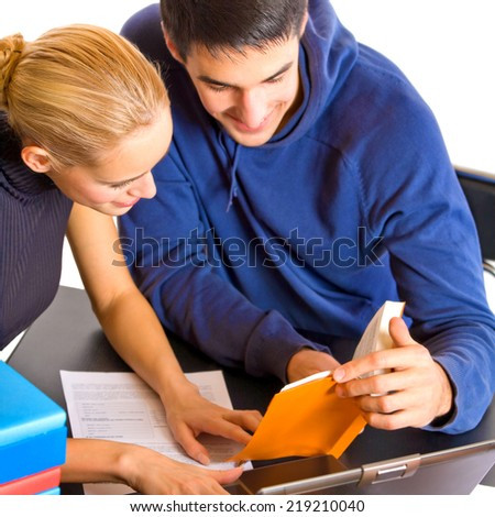 Two young students with books and laptop studying, isolated over white background - stock photo