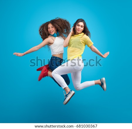 Two young stylish girls jumping for photo in studio on blue background.