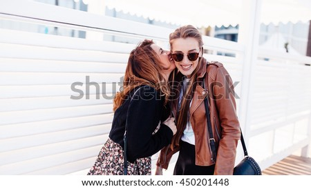 Two young stylish ladies in sunglasses are enjoying their walk outside. One girl in black jacket is kissing another in a cheek - stock photo