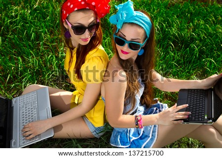 Two young stylish woman using laptops back to back  on a green lawn