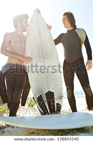 Two young surfer friends standing on the dunes of a white sand beach and getting ready for surfing with their surfing boards and wearing a neoprene rubber suit during a sunny day with a blue sky. - stock photo