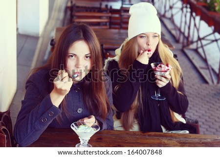 Two young teenage girls eat desserts in the city cafe - stock photo