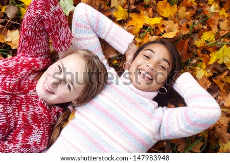 Two young teenager girls friends laying down with their heads together on a bed of autumn brown and yellow leaves, being joyful and laughing while having fun. - stock photo